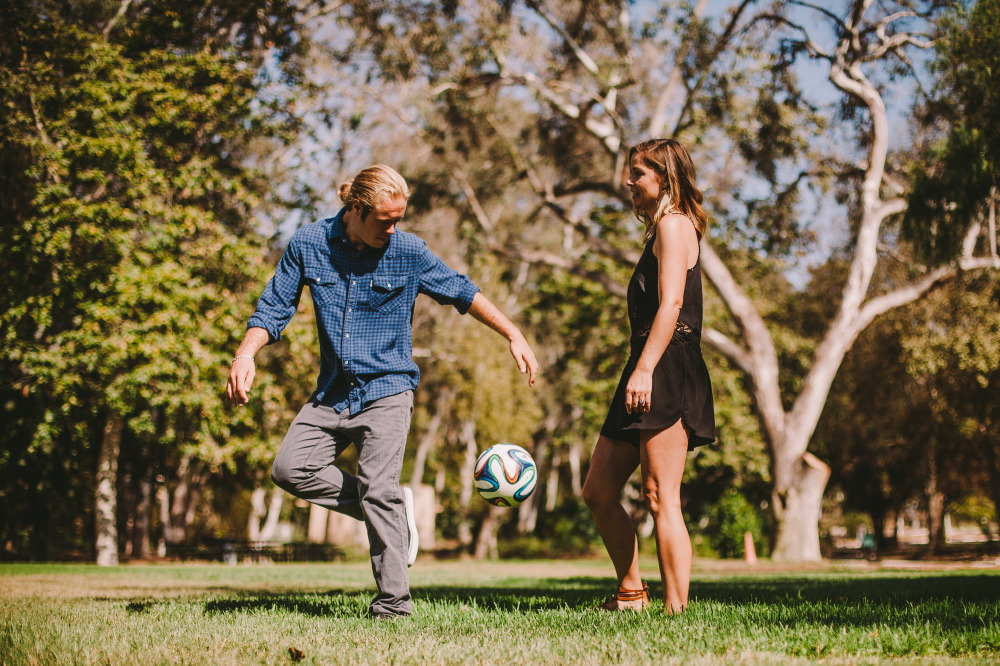 san   diego wedding photographer | blonde man in ponytail playing with soccer ball   with blonde woman in black dress watching him