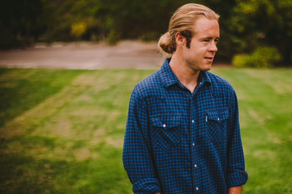 san   diego wedding photographer | blonde man in ponytail and dark blue polo   looking to side