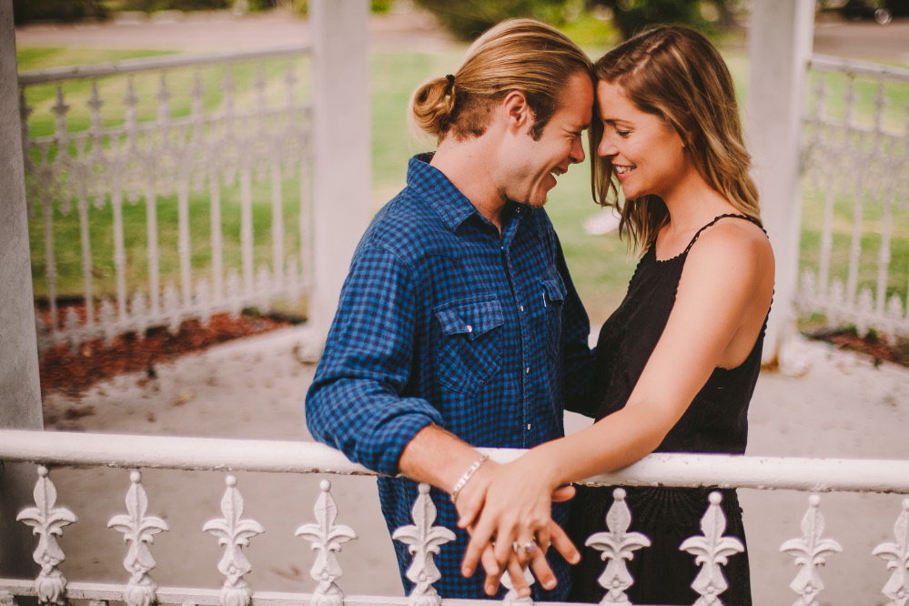 san   diego wedding photographer | blonde woman and blonde man in ponytail and   checkered polo facing each other and holding hands inside white gazebo