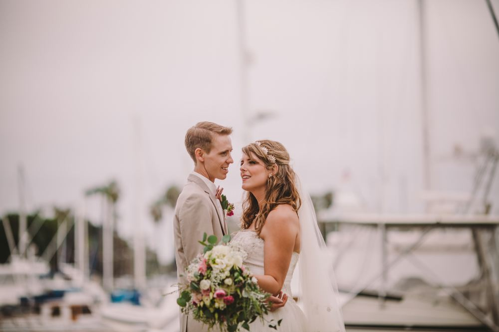 san   diego wedding photographer | man holding woman with bouquet both looking   away