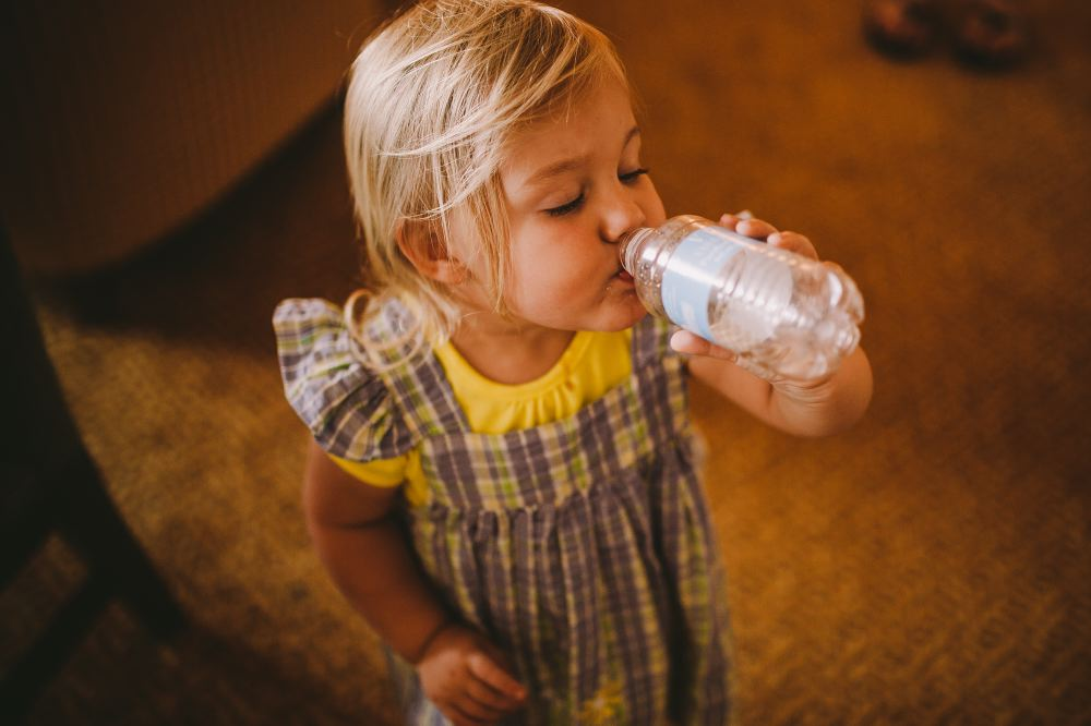 san   diego wedding photographer | child in a blue dress drinking water from a   bottle