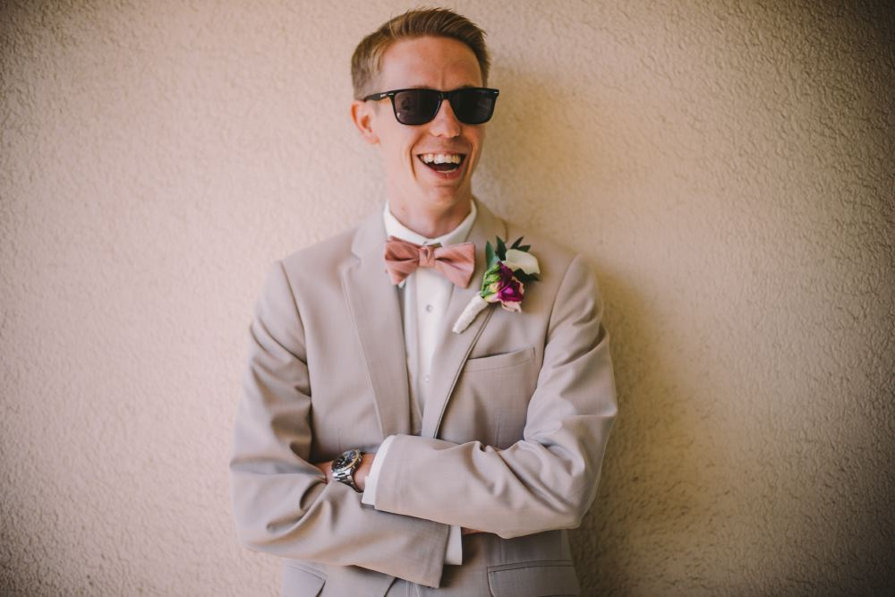 san   diego wedding photographer | man in grey suit and pink bowtie smiling