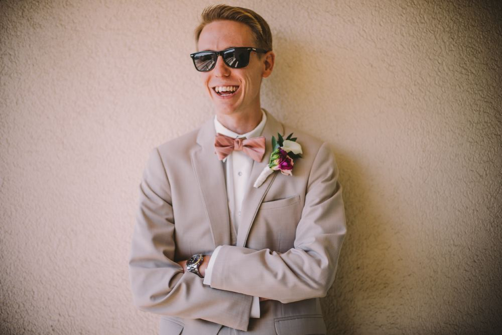 san   diego wedding photographer | man in grey suit and pink bow tie laughing