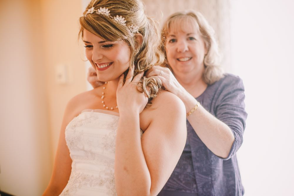 san   diego wedding photographer | bride to be being helped put on necklace