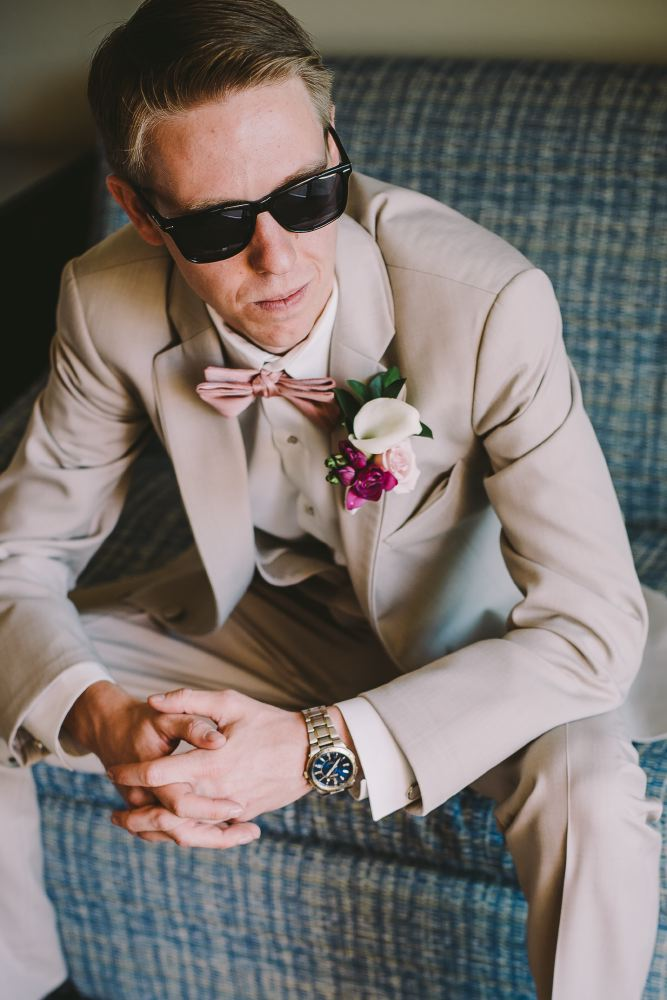san   diego wedding photographer | man in shades and grey suit sitting down looking   down