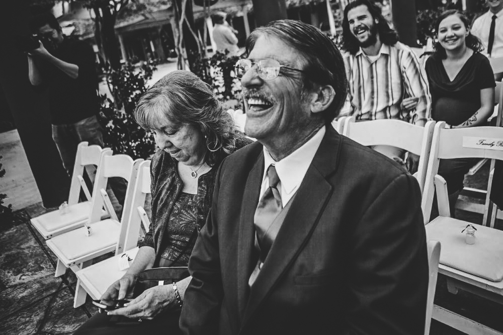 san   diego wedding photographer | monotone shot of man in crowd with glasses   laughing looking in front