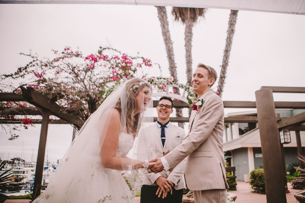 san   diego wedding photographer | bride and groom in grey suit laughing holding   hands with bride