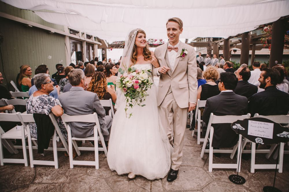 san   diego wedding photographer | bride and groom hand in hand walking up the   aisle with crowd behind