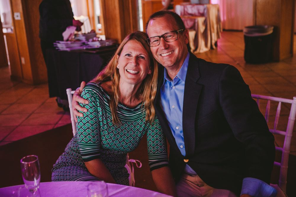 san   diego wedding photographer | middle aged man and woman with man's arm around   woman in green's shoulder