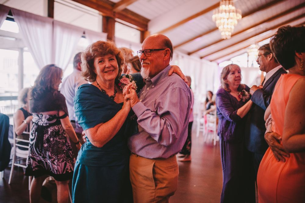 san   diego wedding photographer | middle aged man in purple shirt dancing with   woman in green dress