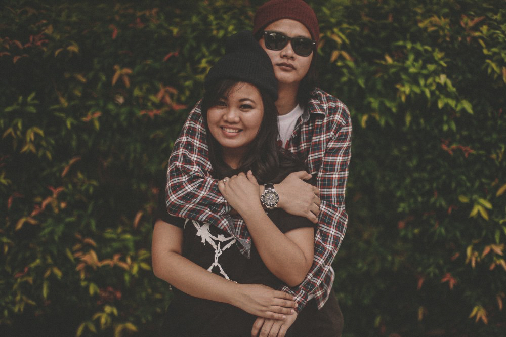 san   diego wedding photographer | man with red beanie and flannel hugging woman   with black beanie and black shirt