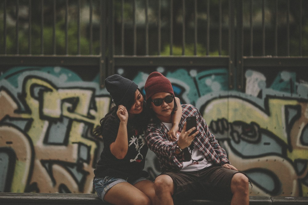 san   diego wedding photographer | man with red beanie and flannel taking selfie   with woman with black beanie and black shirt