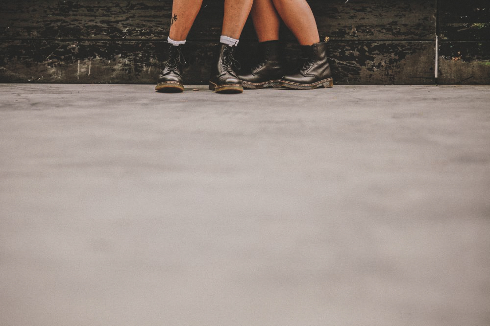 san   diego wedding photographer | two pairs of legs wearing combat boots on cement   ground