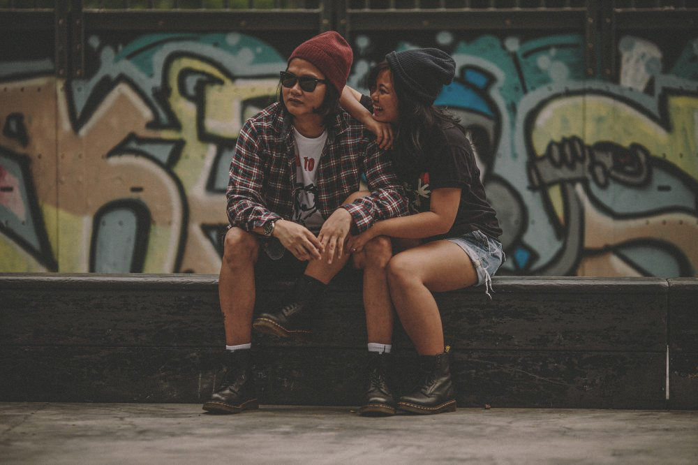 san   diego wedding photographer | woman with black beanie and black shirt resting   arm on shoulder of man with red beanie and flannel and smiling