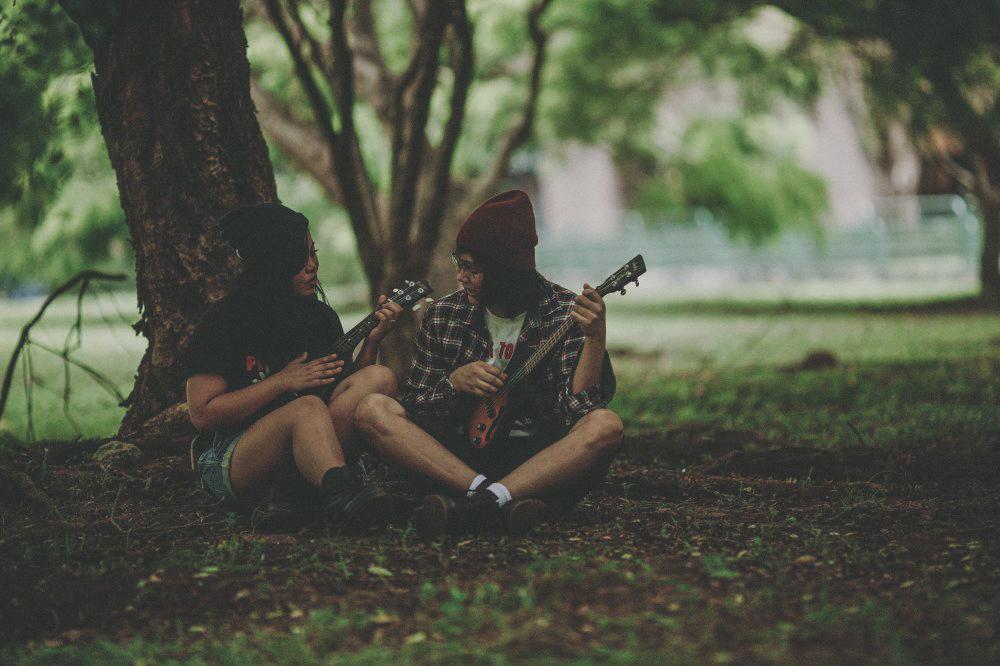 san   diego wedding photographer | man with red beanie and flannel and woman with   black beanie and black shirt playing guitar