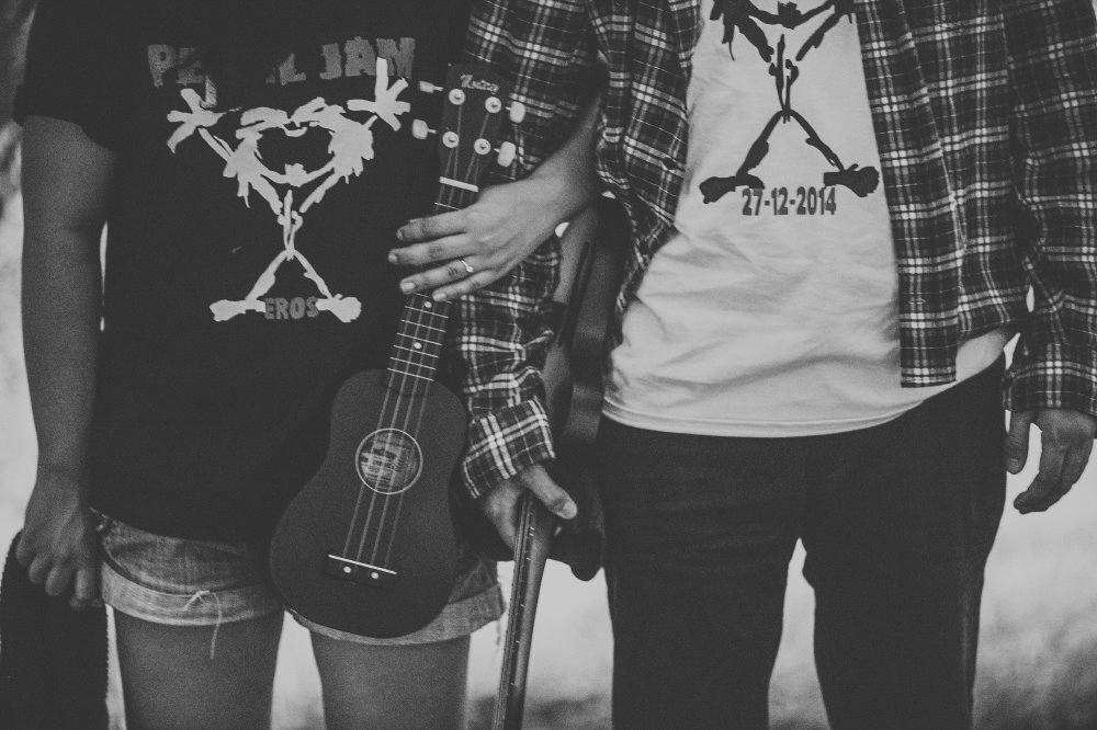 san   diego wedding photographer | monotone neck-down shot of person in denim   shorts holding ukelele crossing arms with person in flannel holding guitar