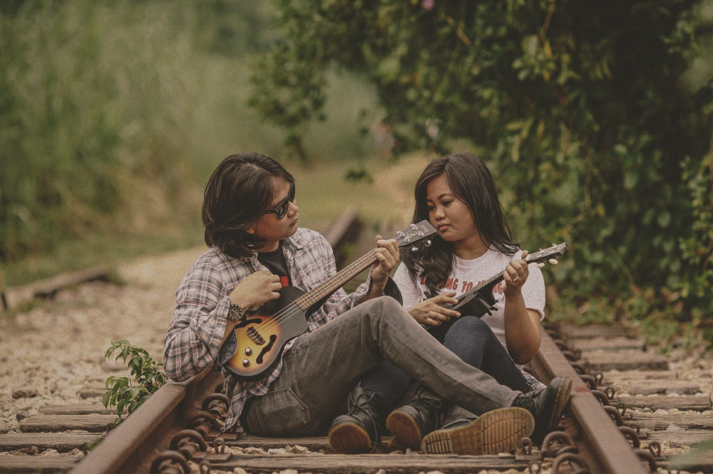san   diego wedding photographer | woman wearing white shirt and man wearing   sunglasses and flannel playing ukeleles on railroad tracks