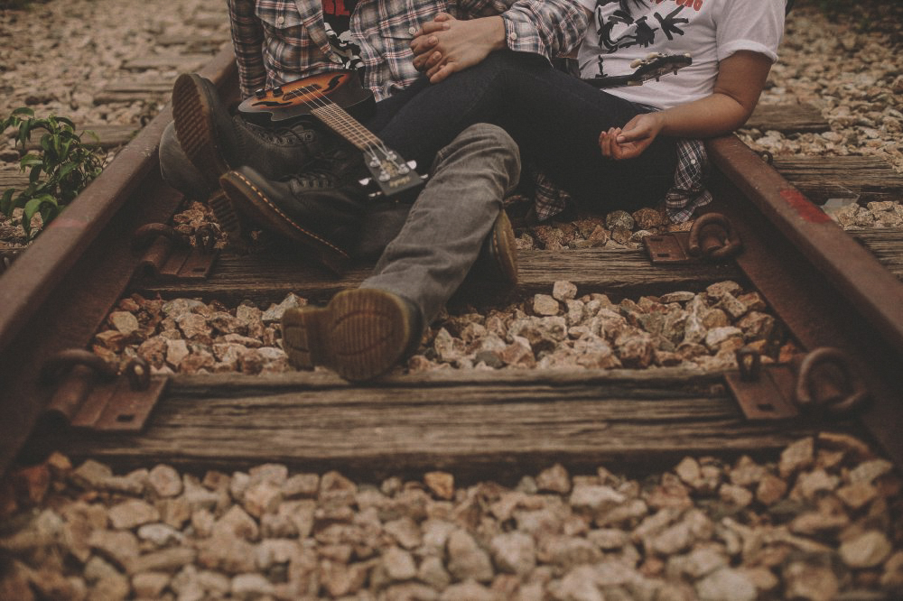 san   diego wedding photographer | neck-down shot of person in flannel with guitar   holding hands with person in white on railroad tracks