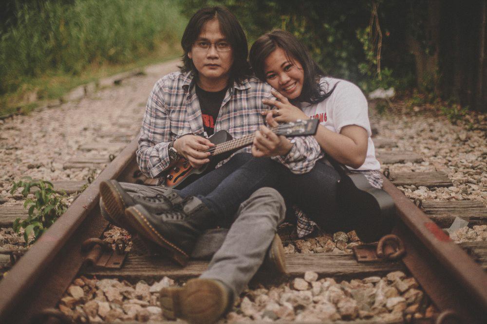 san   diego wedding photographer | man wearing flannel playing the guitar woman   wearing white shirt sitting on railroad tracks