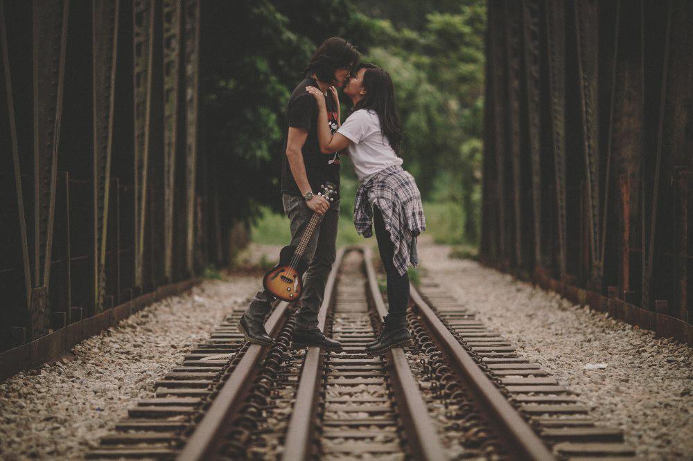 san   diego wedding photographer | man holding guitar kissing woman wearing white   shirt on railroad tracks