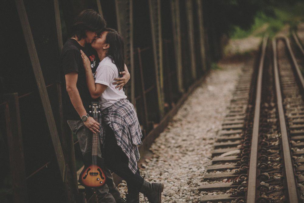 san   diego wedding photographer | man holding guitar kissing woman in white shirt   beside railroad tracks