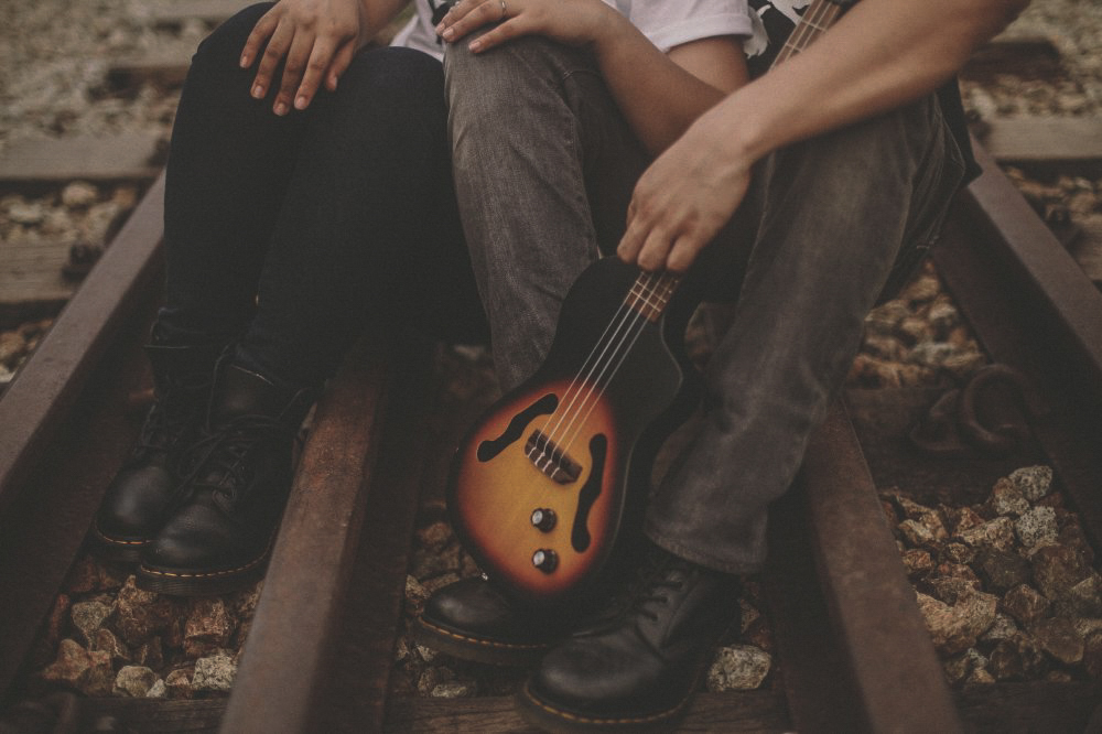 san   diego wedding photographer | bottom-half shot of people wearing combat boots   and sitting on railroad tracks with small guitar