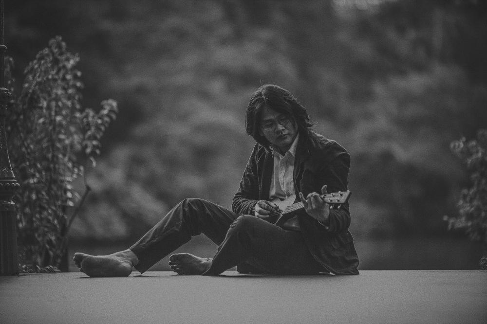 san   diego wedding photographer | monotone shot of man with eyeglasses sitting on   ground barefoot and playing ukelele