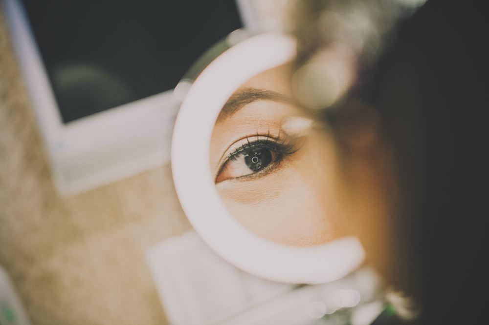 san   diego wedding photographer | eyeshadow being applied on eye looking at white   circular mirror