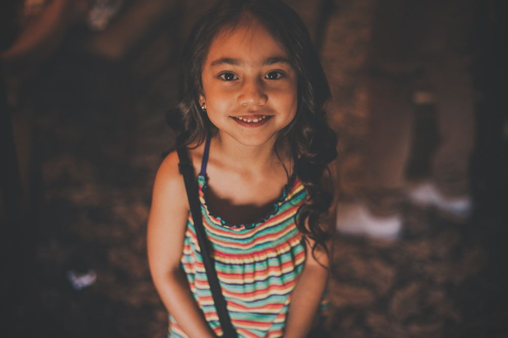 san   diego wedding photographer | girl with long hair and striped rainbow dress   smiling at camera