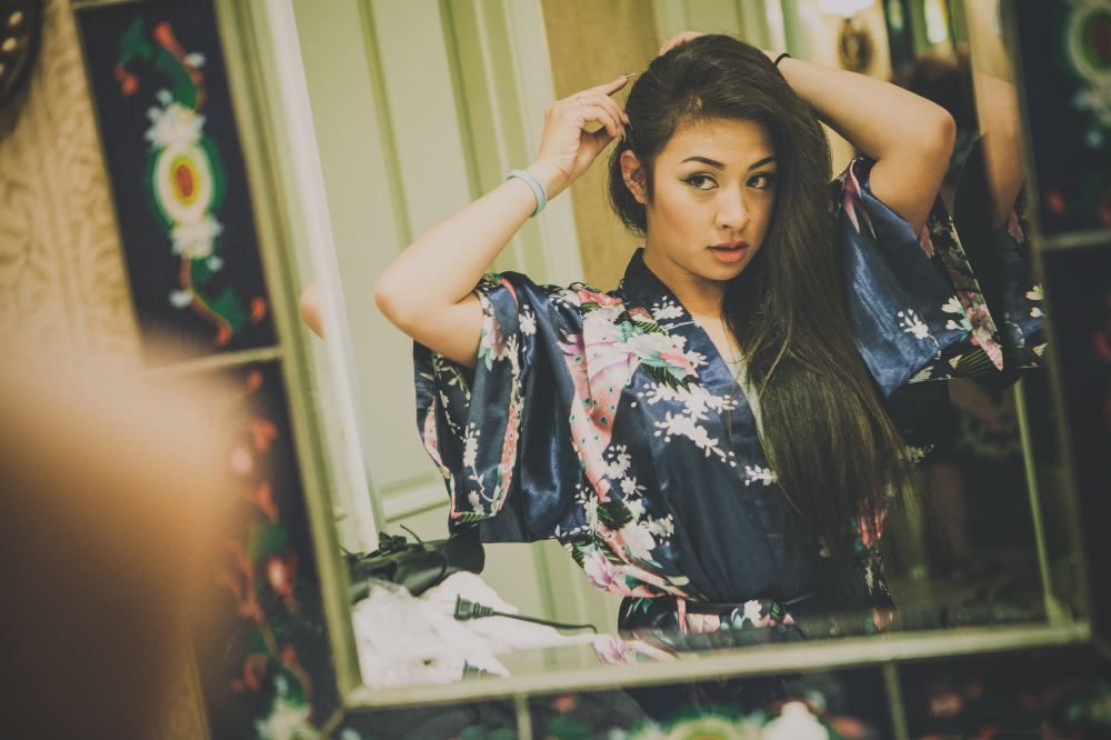 san   diego wedding photographer | woman in dark blue floral robe looking at mirror   and styling hair