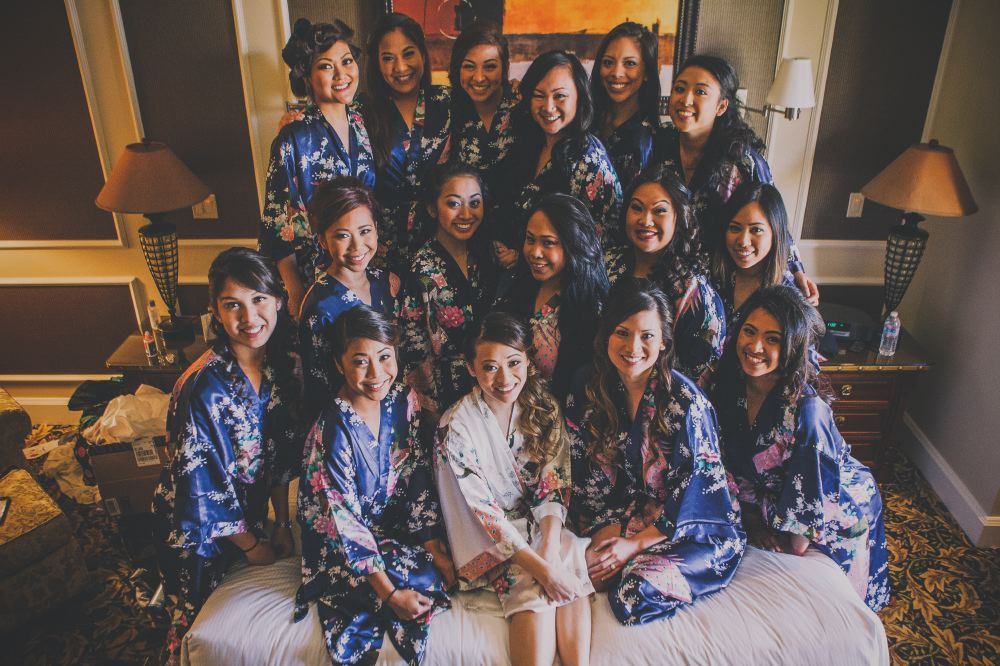 san   diego wedding photographer | group shot of women in dark blue floral robes   with woman in white floral robe on bed