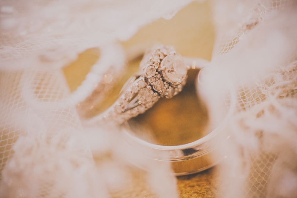 san   diego wedding photographer | wedding rings with white lace out of focus in   foreground