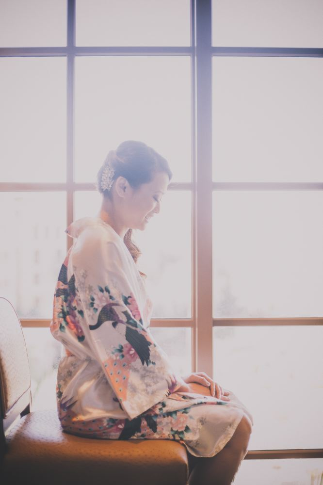san   diego wedding photographer | side view of woman in white floral robe and   curly ponytail sitting on beige chair