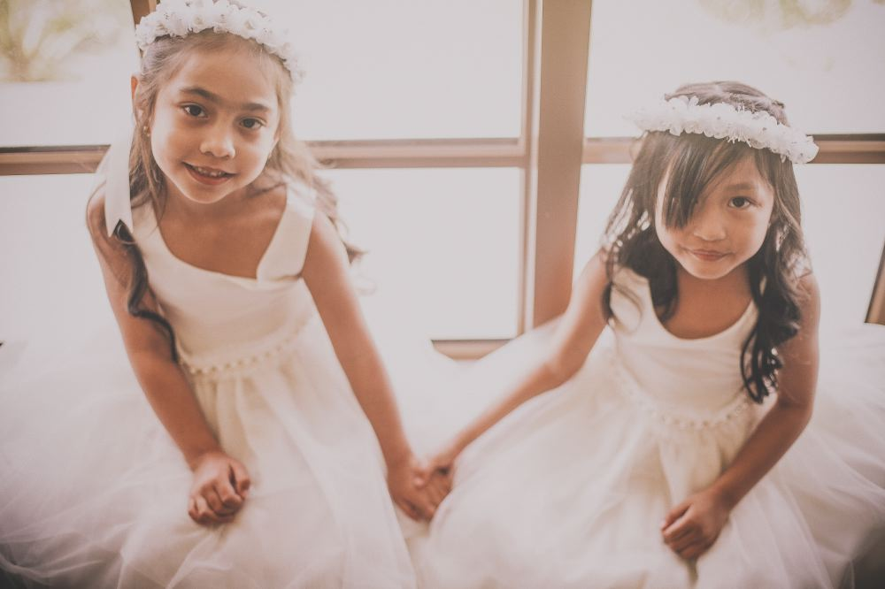 san   diego wedding photographer | two girls in white dresses and white floral   crowns holding hands and smiling at camera