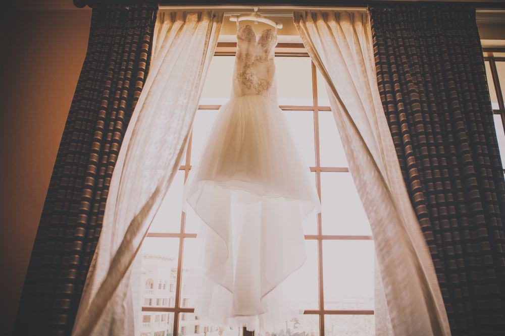 san   diego wedding photographer | mermaid strapless wedding dress hanging on   curtain rod in front of window