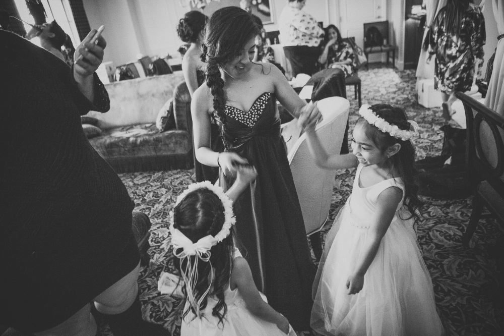 san   diego wedding photographer | monotone shot of two girls in white dresses and   white floral crowns holding hands with woman in strapless dress