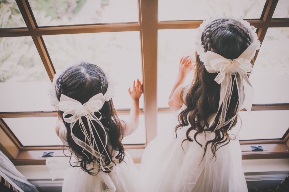 san   diego wedding photographer | back of two girls in white dresses and white   floral crowns looking outside windows