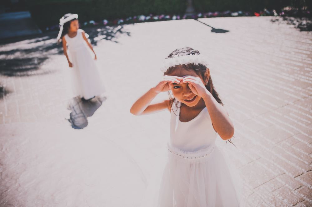 san   diego wedding photographer | girl in white dress and white floral crown   looking at camera and shielding eyes against sunlight