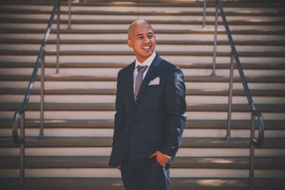 san   diego wedding photographer | bald man in dark blue suit looking to his left   and smiling in front of staircase