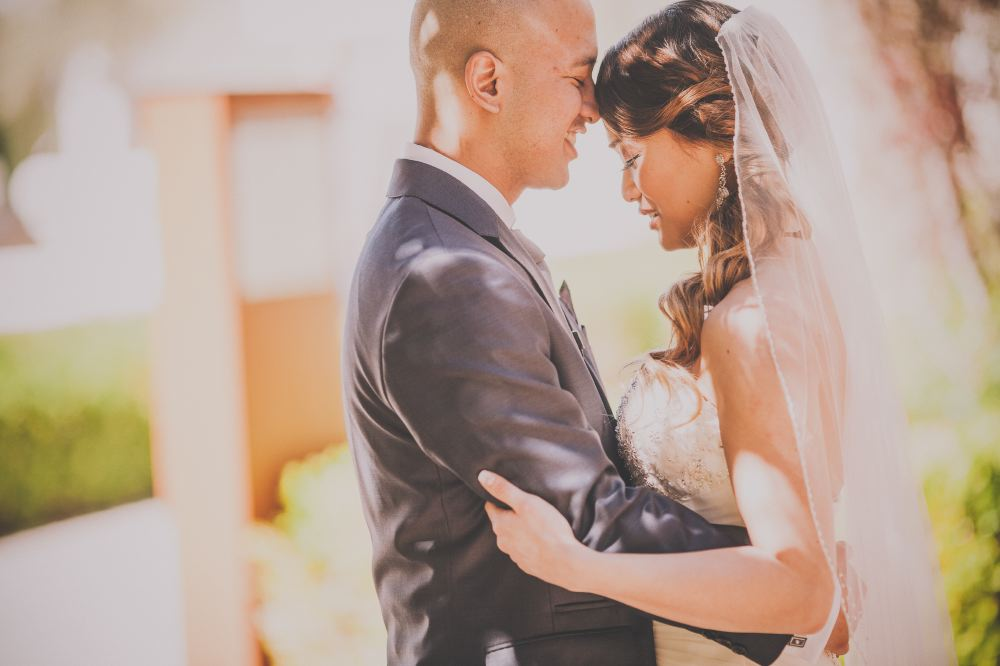 san   diego wedding photographer | bald man in suit and woman in white embracing   with man's nose on woman's forehead