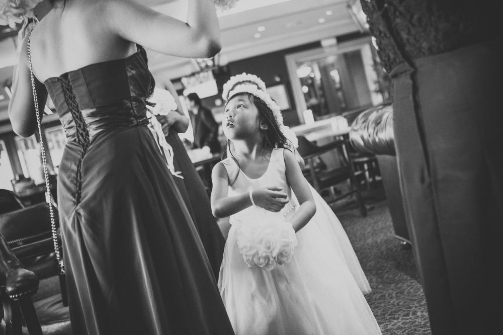 san   diego wedding photographer | monotone shot of girl in white dress holding   white bouquet and looking up at woman in strapless dress