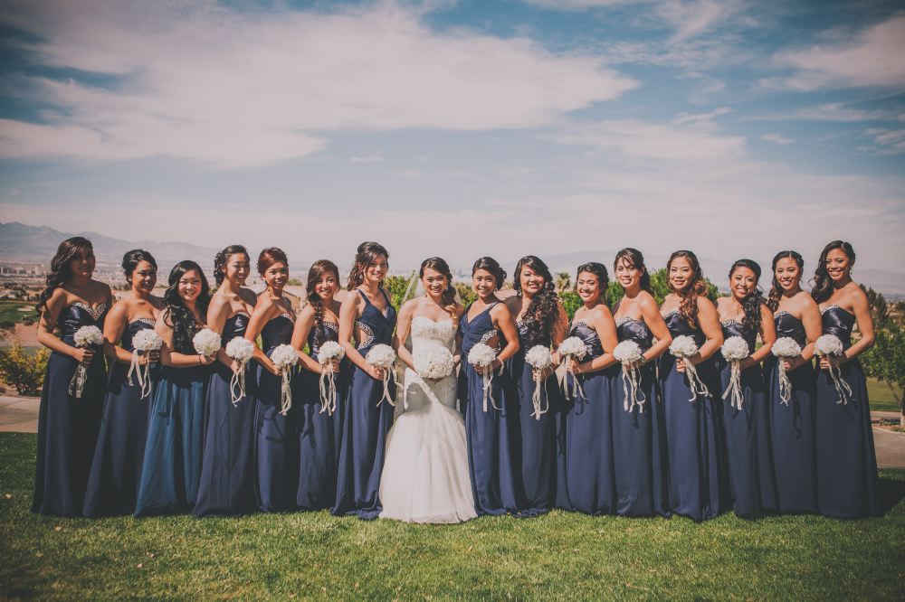 san   diego wedding photographer | outdoor group shot of bride with bridesmaids and   maid of honor in dark blue sleeveless dresses holding bouquets and smiling
