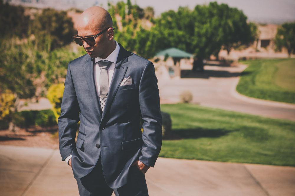 san   diego wedding photographer | bald man wearing dark blue suit and sunglasses   looking down with hands in his pockets