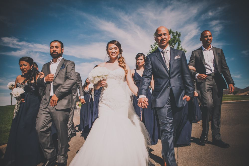 san   diego wedding photographer | bald groom in dark blue suit holding hands with   bride with curly ponytail and walking with bridesmaids and groomsmen in   background