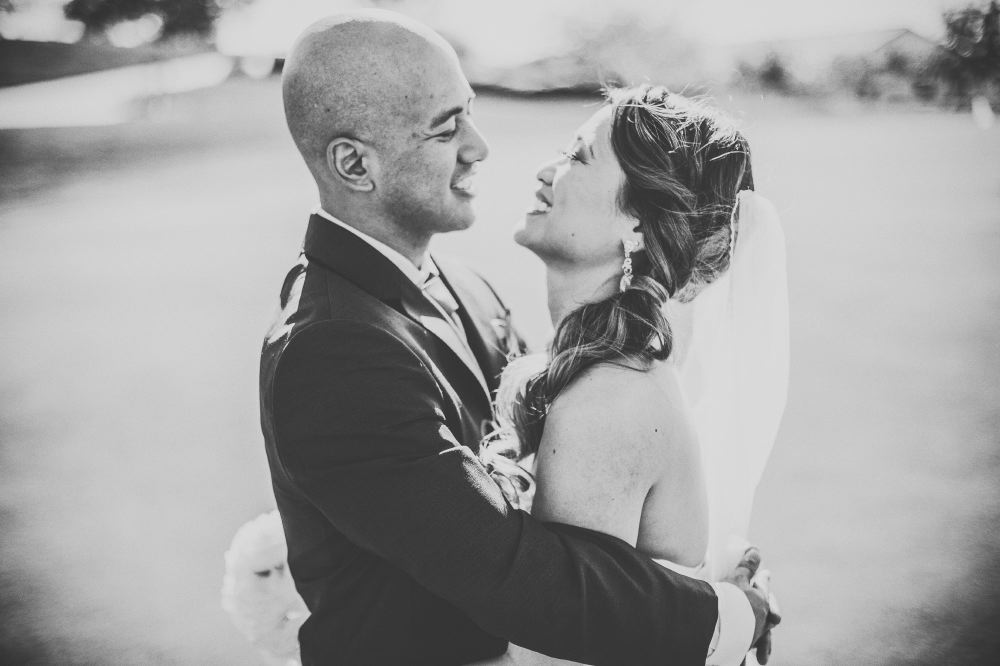 san   diego wedding photographer | monotone shot of bald groom hugging bride with   curly ponytail and smiling