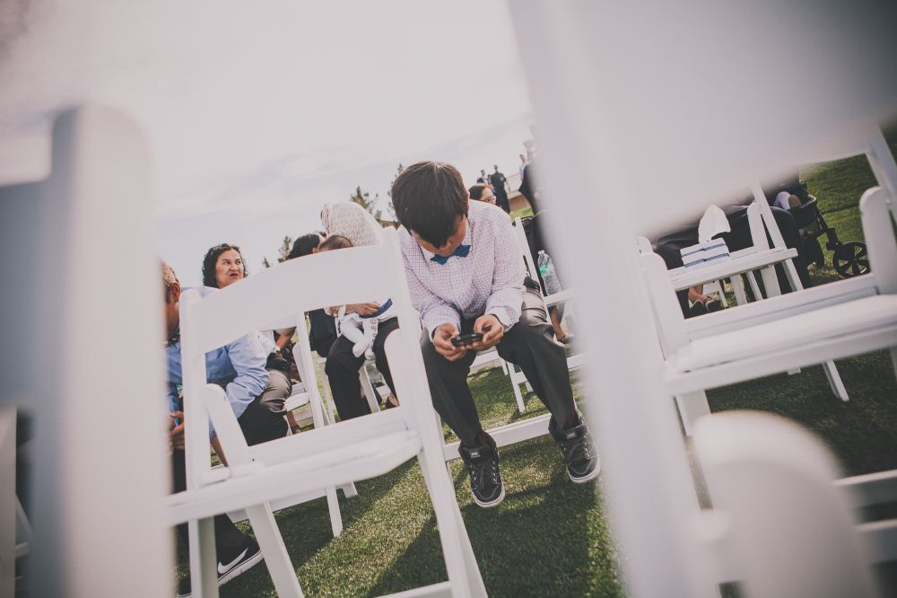san   diego wedding photographer | boy with teal bowtie sitting and using his phone   with white chairs out of focus in foreground