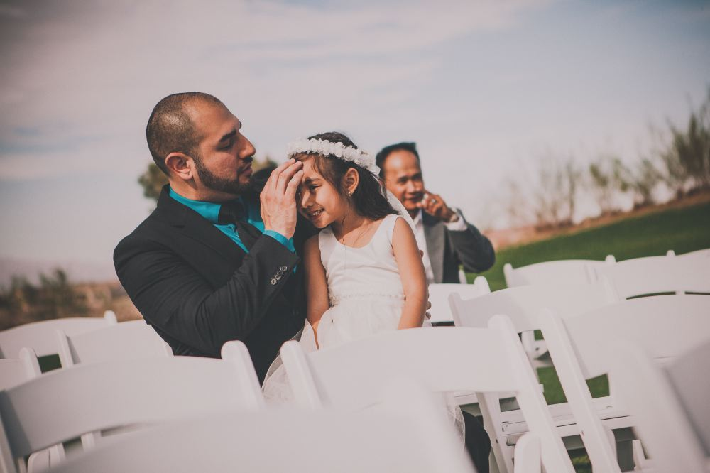 san   diego wedding photographer | young girl wearing white dress sitting on lap of   man in teal polo and black suit
