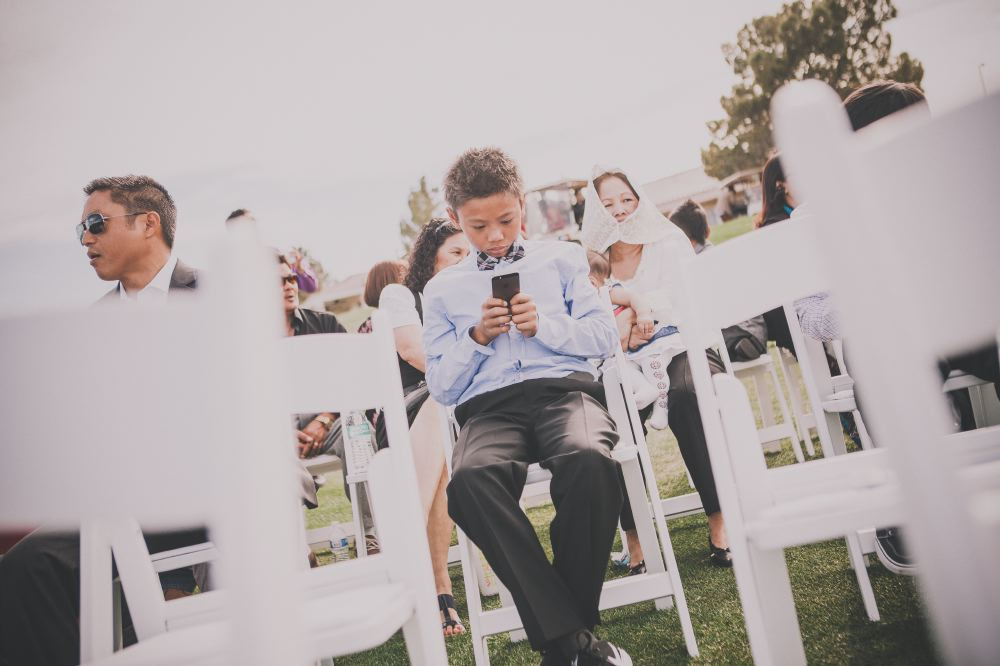 san   diego wedding photographer | boy in blue suit and checkered bowtie sitting   and using his phone with white chairs out of focus in foreground