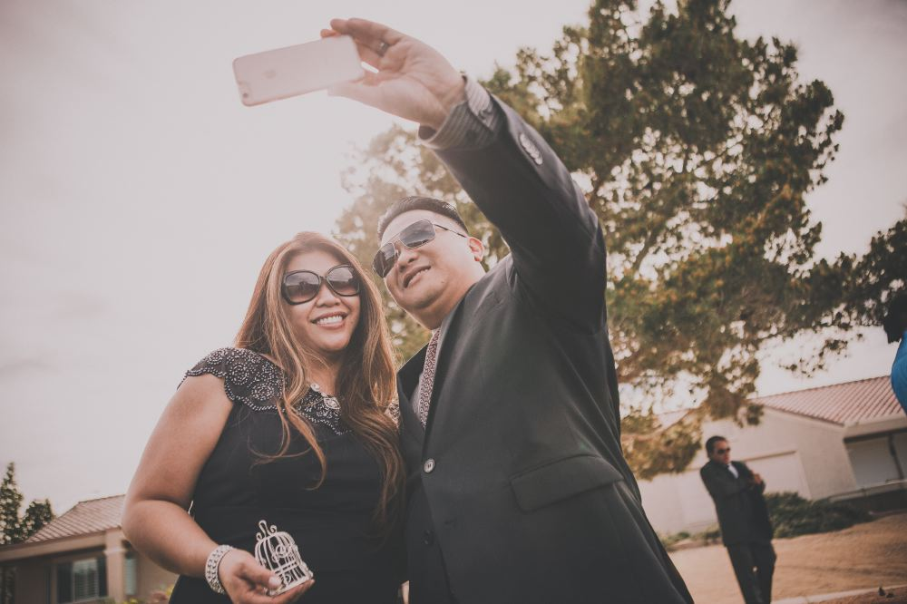 san   diego wedding photographer | man with   black sunglasses and black suit taking a selfie with woman with   sunglasses in black dress
