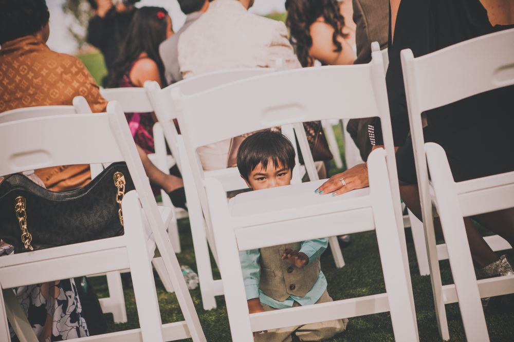 san   diego wedding photographer | boy in teal suit kneeling on grass in front of   white chair and looking at camera